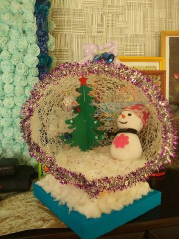Это новогодняя экспозиция, представлена как елочная игркшка-шар, сделанный из ниток, в котором имеется елка(аппликации из цветной бумаги) и снеговик(поделка из носка)
