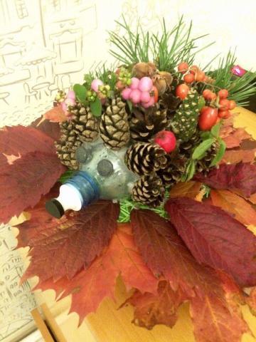 Работа сделана из шишек, листьев, пластиковой бутылки с песком, украшены травой и ягодками.